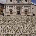 La scenografica scalinata d'accesso alla chiesa di San Bernardino e l'imponente facciata in pietra calcarea, suddivisa in tre livelli orizzontali.